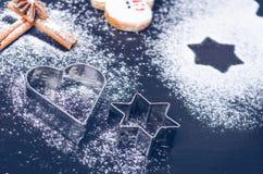 Украшение и печенья рождества Рука женщины брызгая сахар на печенья Мука и специи для выпечки на темном backg Стоковое Фото