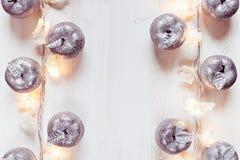 Украшение и света яблок рождества серебряное горя на белой деревянной предпосылке Стоковые Фото