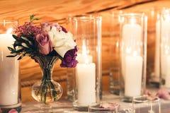 Украшение на таблице: свечи в стеклах, фиолетовых цветках в вазах стоковое фото