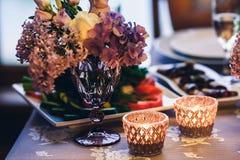 Украшение на таблице: свечи в стеклах, фиолетовых цветках в вазах стоковые изображения