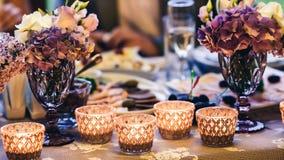 Украшение на таблице: свечи в стеклах, фиолетовых цветках в вазах стоковые изображения rf