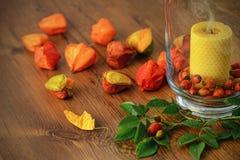 Украшение осени с плодами шиповника и свечой горения в стекле Стоковая Фотография