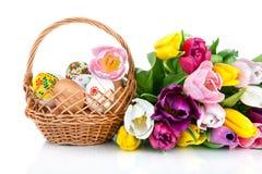 Украшение пасхального яйца в цветках корзины и тюльпана изолированных на wh Стоковые Фото