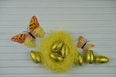 Украшение пасхи весеннего времени с желтым гнездом заполнило с сияющими золотыми яичками цвета и украшениями формы бабочки Стоковая Фотография