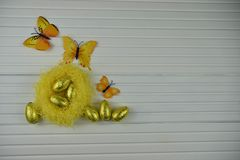 Украшение пасхи весеннего времени с желтым гнездом заполнило с яичками золотого цвета сияющими и украшениями формы бабочки Стоковое Изображение