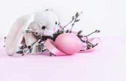 Украшение пасхи зайчика пасхи и вербы pussy с яйцом и розовая лента на розовой предпосылке стоковое фото
