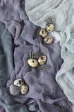 Украшение пасхи с яичками триперсток на серой предпосылке ткани стоковые изображения