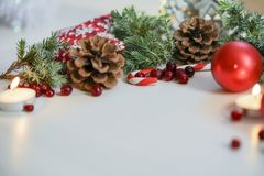 Украшение 2018 рождества для таблицы, шариков рождественской елки красных, горя свечи с ветвью ели и свечи на деревянной предпосы Стоковая Фотография