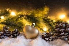 Украшение рождества зимы с сердцем сформировало орнамент рождества, конусы, ветвь ели и накаляя света Стоковые Изображения