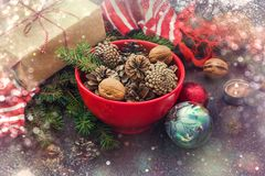 Украшение рождества - красный шар вполне ель-конусов, подарочной коробки обернутой в бумаге kraft, ветвях сосны, свече, гайках, а Стоковые Фото