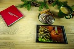 Украшение рождества на деревенской деревянной доске с таблеткой, Стоковые Фото