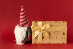 Украшение рождества с гномом и подарочная коробка на красном backgrou стоковые изображения