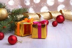 Украшение рождества с подарочными коробками, красочными шариками рождества и рождественской елкой на расплывчатом, сверкнающ и фа Стоковые Изображения