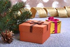 Украшение рождества с подарочными коробками, рождественской елкой и конусами на расплывчатой, сверкная и фантастичной предпосылке Стоковое фото RF