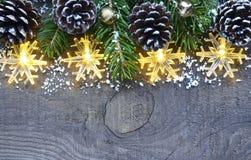Украшение рождества с светами гирлянды, конусами сосны и елью на старой деревянной предпосылке граница предпосылки кладет тесемки Стоковое фото RF