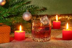 Украшение рождества с стеклом вискиа или коньяка, свечей рождества, дерева и подарочной коробки на сверкная предпосылке Стоковое фото RF
