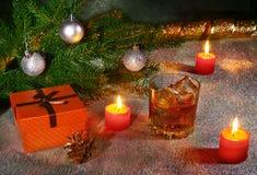 Украшение рождества с стеклом вискиа или коньяка, свечей рождества, дерева и подарочной коробки на сверкная предпосылке Стоковое Фото