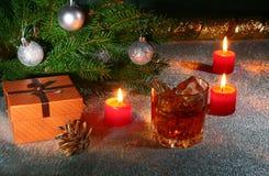 Украшение рождества с стеклом вискиа или коньяка, свечей рождества, дерева и подарочной коробки на сверкная предпосылке Стоковая Фотография RF