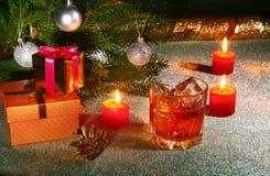 Украшение рождества с стеклом вискиа или коньяка, свечей рождества, дерева и подарочной коробки на сверкная предпосылке Стоковые Фотографии RF