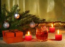 Украшение рождества с стеклом вискиа или коньяка, свечей рождества, дерева и подарочной коробки на сверкная предпосылке Стоковое Изображение