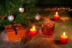 Украшение рождества с стеклом вискиа или коньяка, свечей рождества, дерева и подарочной коробки на сверкная предпосылке Стоковые Фото