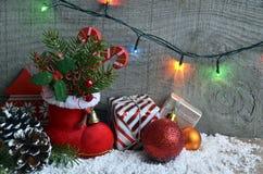 Украшение рождества: красные ботинок ` s Санты, ель, гирлянда, подарки, конус сосны и шарики рождества на деревянной предпосылке  Стоковое Изображение RF