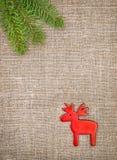 Украшение рождества с ветвью ели и красные олени на мешковине Стоковая Фотография