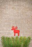 Украшение рождества с ветвью ели и красные олени на мешковине Стоковое Фото
