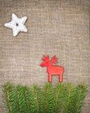 Украшение рождества с ветвью ели и красные олени на мешковине Стоковое фото RF