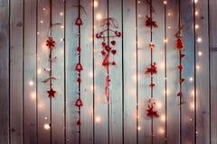 Украшение рождества с красными и белыми цветами с формами сердец, ангелов и оленей вися на белой деревянной стене текстуры Стоковые Изображения