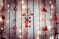 Украшение рождества с красными и белыми цветами с формами сердец, ангелов и оленей вися на белой деревянной стене текстуры Стоковое фото RF