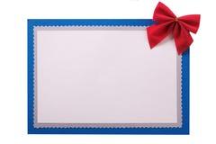 Украшение смычка рождественской открытки красное изолировало голубую рамку стоковые изображения