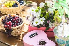 Украшение таблицы партии пикника: корзины с плодоовощами на деревянном столе, цветках, розовой малой гитаре и pinwheel стоковые изображения rf