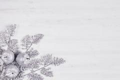 Украшение sprigs и яблок рождества серебряное на деревянной белой предпосылке Стоковые Фото