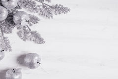 Украшение sprigs и яблок рождества серебряное на деревянной белой предпосылке Стоковое Фото