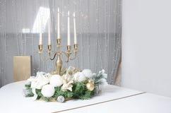 Украшения и золотой подсвечник Нового Года с горящими свечами стоят на поверхности белого рояля стоковые изображения rf