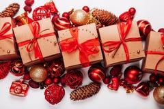 Украшения и подарки рождества на белой предпосылке Конусы, шарики красного цвета и подарки золота бежевые украшенные с красной ле Стоковая Фотография