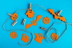 Украшения на хеллоуин - оранжевые бумажные призраки, тыквы и летучие мыши на веревочке с штырями на голубой предпосылке стоковое изображение