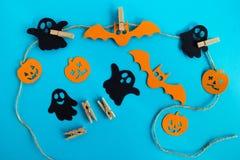 Украшения на хеллоуин - призраки черноты и апельсина бумажные, тыквы и летучие мыши на веревочке с штырями на голубой предпосылке стоковые фотографии rf