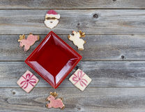 Украшения печений рождества вокруг красной плиты на древесине Стоковое фото RF