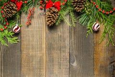 Украшения рождества и ветви ели на предпосылке деревянной доски с космосом экземпляра Стоковые Фото