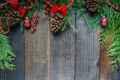 Украшения рождества и ветви ели на предпосылке деревянной доски с космосом экземпляра Стоковое Изображение