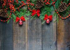 Украшения рождества и ветви ели на предпосылке деревянной доски с космосом экземпляра Стоковая Фотография RF