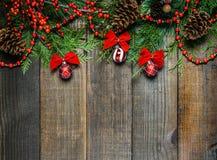 Украшения рождества и ветви ели на предпосылке деревянной доски с космосом экземпляра Стоковые Изображения RF