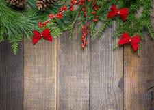 Украшения рождества и ветви ели на предпосылке деревянной доски с космосом экземпляра Стоковое Изображение RF