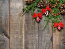 Украшения рождества и ветви ели на предпосылке деревянной доски с космосом экземпляра Стоковое Фото
