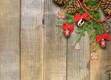 Украшения рождества и ветви ели на предпосылке деревянной доски с космосом экземпляра Стоковая Фотография