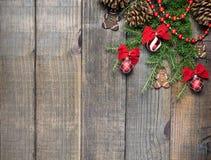 Украшения рождества и ветви ели на предпосылке деревянной доски с космосом экземпляра Стоковые Изображения