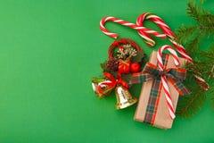 Украшения рождества и коробка праздничного подарка в бумаге ремесла на зеленой предпосылке, взгляд сверху, космосе экземпляра Стоковые Фото