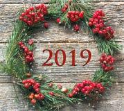 Украшения рождества, красный цвет рябины и ветви ели на деревянной предпосылке Концепция Нового Года надписи 2019 стоковое фото rf